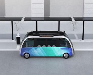 ソーラーパネルが備えているバス停に停車中の自動運転シャトルバス。省エネ交通機関のコンセプトの写真素材 [FYI04646957]