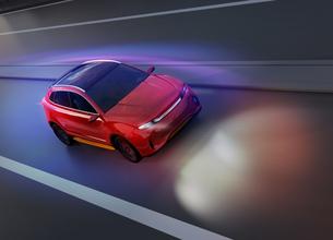 夜間道路に走行している赤色電動SUVのイメージの写真素材 [FYI04647098]