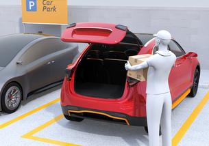 配達員が駐車場にあるクルマのトランクを開け、車内配達サービスを行う。ラストワンマイルコンセプトの写真素材 [FYI04647179]