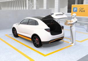 配達員が駐車場にあるクルマのトランクを開け、車内配達サービスを行う。ラストワンマイルコンセプトの写真素材 [FYI04647182]