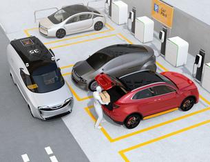 配達員が駐車場にあるクルマのトランクを開け、車内配達サービスを行う。ラストワンマイルコンセプトの写真素材 [FYI04647193]