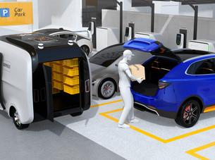 配達員が駐車場にあるクルマのトランクを開け、車内配達サービスを行う。ラストワンマイルコンセプトの写真素材 [FYI04647195]