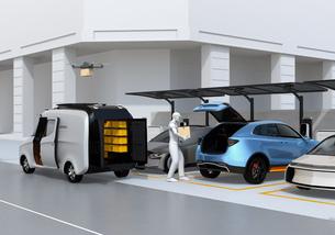 駐車場に配達員が車のトランクを開け、車内配達する同時にドローンも配達する。ラストワンマイルコンセプトの写真素材 [FYI04647203]