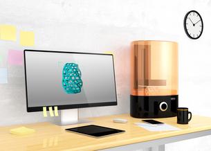 光造形式3Dプリンタとノートパソコン。パソコン画面に2Dモデルが表示されている。の写真素材 [FYI04647700]