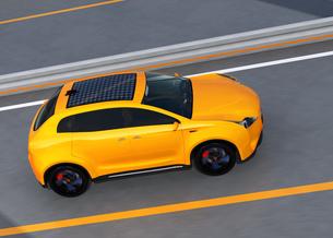 高速道路に走行する黄色の電気自動車SUVの写真素材 [FYI04647971]