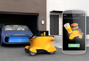 駐車場前の黄色いハンバーガーの自動運転宅配車とスマホオーダー画面イメージの写真素材 [FYI04648177]