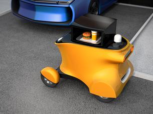 駐車場前の黄色いハンバーガーの自動運転配送車の写真素材 [FYI04648179]