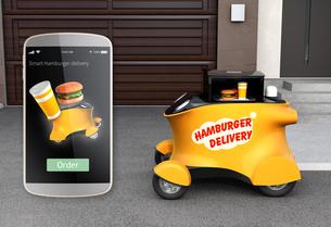 駐車場前の黄色いハンバーガーの自動運転宅配車とスマホオーダー画面イメージの写真素材 [FYI04648187]