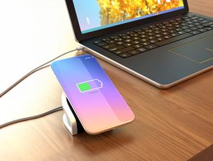 ワイヤレス充電器に充電中のスマートフォン。充電器がノートパソコンと接続しているの写真素材 [FYI04648316]