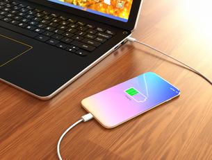 ノートパソコンと接続して充電しているスマートフォンのイメージの写真素材 [FYI04648317]