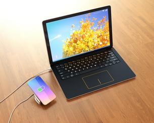 ワイヤレス充電器に充電中のスマートフォン。充電器がノートパソコンと接続しているの写真素材 [FYI04648319]