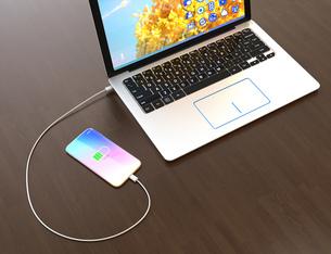 ワイヤレス充電器に充電中のスマートフォン。充電器がノートパソコンと接続しているの写真素材 [FYI04648320]