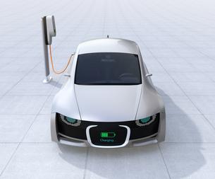 充電中の電気自動車のフロント部に充電状態が表示し、車と人のコミュニケーションのコンセプトの写真素材 [FYI04648429]