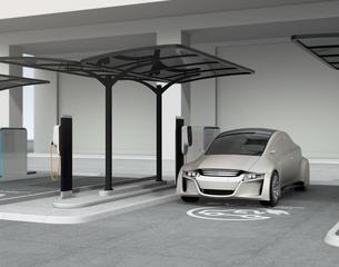 公共施設の充電スタンドに充電しているシルバー色の電気自動車の写真素材 [FYI04648493]