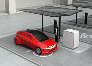 公共施設の充電スタンドに充電している赤色の電気自動車の写真素材 [FYI04648501]