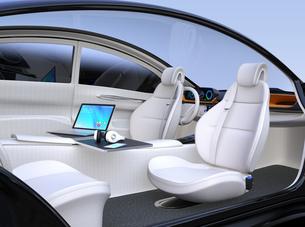 自動運転車の前列シートが後ろに向かい、収納式テーブルにノートPC。モバイルオフィスのコンセプトの写真素材 [FYI04648541]