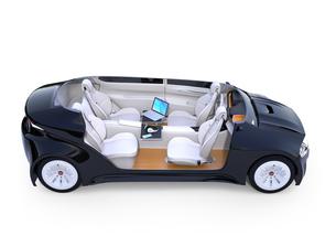 自動運転車の対面式シートレイアウト。収納式テーブルにノートPC。モバイルオフィスのコンセプトの写真素材 [FYI04648549]