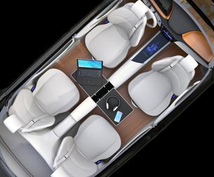 自動運転車の前列シートが後ろに向かい、収納式テーブルにノートPC。モバイルオフィスのコンセプトの写真素材 [FYI04648559]