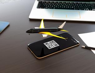 卓上にあるスマートフォンから飛び立つ飛行機。モバイルチェックインのコンセプトの写真素材 [FYI04648658]