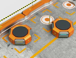 ワイヤレス充電スタンドに充電しているオレンジ色の物流運搬支援ロボットの写真素材 [FYI04648838]