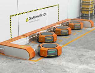 ワイヤレス充電スタンドに充電しているオレンジ色の物流運搬支援ロボットの写真素材 [FYI04648839]
