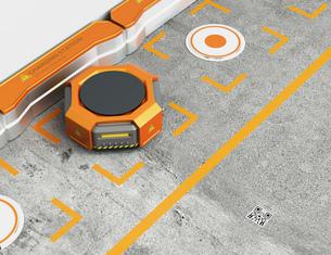 ワイヤレス充電スタンドに充電しているオレンジ色の物流運搬支援ロボットの写真素材 [FYI04648840]