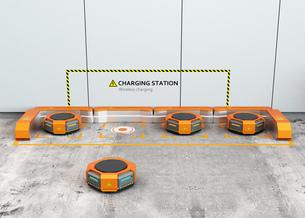 ワイヤレス充電スタンドに充電しているオレンジ色の物流運搬支援ロボットの写真素材 [FYI04648841]