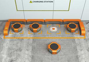 ワイヤレス充電スタンドに充電しているオレンジ色の物流運搬支援ロボットの写真素材 [FYI04648857]