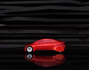 黒い背景の前に止まっている赤色の電気自動車の写真素材 [FYI04648896]