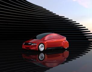 黒い背景の前に止まっている赤色の電気自動車の写真素材 [FYI04648899]