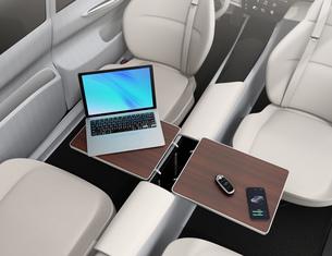 自動運転車のインテリアイメージ。収納式のテーブルにノートPC、スマホとスマートキーが置かれているの写真素材 [FYI04648920]