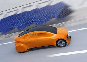 高速道路に走行している自動運転電気自動車。道路側に太陽光電池が設置されているの写真素材 [FYI04648926]