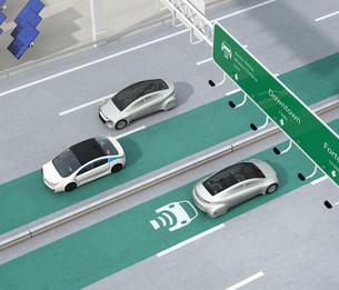 高速道路非接触充電優先レーンに走行している電気自動車。道路側に太陽光発電設備が設置されているの写真素材 [FYI04648937]