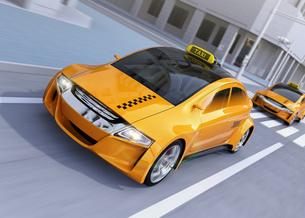 交差点を通過している黄色のタクシーのイメージの写真素材 [FYI04648958]