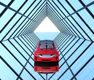 左右対称のガラス張りトンネルにある赤色の自動運転車の写真素材 [FYI04648970]