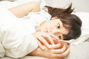 寝る前に携帯を使う若い女性の写真素材 [FYI04655705]