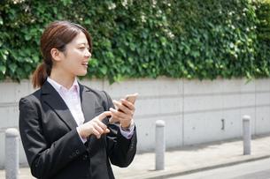 スマホで場所を探す若いビジネスウーマンの写真素材 [FYI04655722]