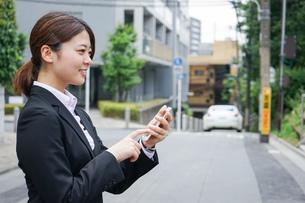 スマホで場所を探す若いビジネスウーマンの写真素材 [FYI04655724]