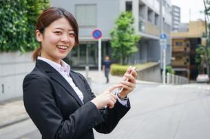 スマホで場所を探す若いビジネスウーマンの写真素材 [FYI04655727]