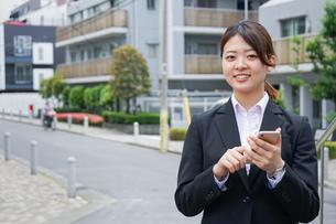 スマホで場所を探す若いビジネスウーマンの写真素材 [FYI04655728]