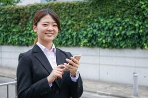 スマホで場所を探す若いビジネスウーマンの写真素材 [FYI04655729]