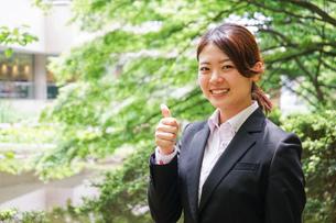 グッドサインをする若いビジネスウーマンの写真素材 [FYI04655777]