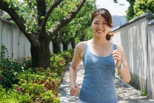 都会をランニングする若い女性の写真素材 [FYI04655836]