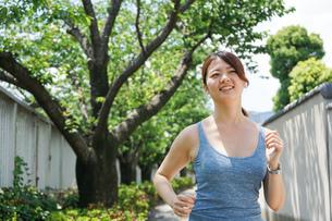 都会をランニングする若い女性の写真素材 [FYI04655838]