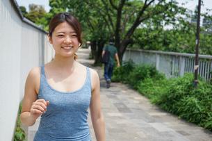 都会をランニングする若い女性の写真素材 [FYI04655845]