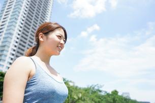 都会をランニングする若い女性の写真素材 [FYI04655852]