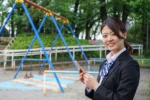 笑顔でスマホを使う制服姿の学生の写真素材 [FYI04655882]