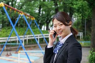 笑顔でスマホを使う制服姿の学生の写真素材 [FYI04655888]