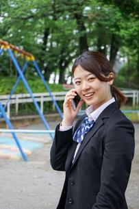 笑顔でスマホを使う制服姿の学生の写真素材 [FYI04655889]