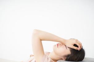 体調不良で横たわる若い女性の写真素材 [FYI04655964]